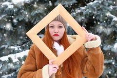 Το όμορφο πορτρέτο γυναικών στο χειμώνα υπαίθριο, κοιτάζει μέσω ξύλινου Στοκ Φωτογραφία