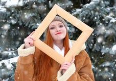 Το όμορφο πορτρέτο γυναικών στο χειμώνα υπαίθριο, κοιτάζει μέσω του ξύλινου πλαισίου, χιονώδη δέντρα έλατου στη δασική, μακριά κό Στοκ εικόνα με δικαίωμα ελεύθερης χρήσης