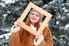 Το όμορφο πορτρέτο γυναικών στο χειμώνα υπαίθριο, κοιτάζει μέσω του ξύλινου πλαισίου, χιονώδη δέντρα έλατου στη δασική, μακριά κό Στοκ Φωτογραφία