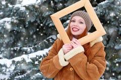 Το όμορφο πορτρέτο γυναικών στο χειμώνα υπαίθριο, κοιτάζει μέσω του ξύλινου πλαισίου, χιονώδη δέντρα έλατου στη δασική, μακριά κό Στοκ φωτογραφία με δικαίωμα ελεύθερης χρήσης