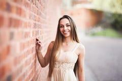 Το όμορφο προκλητικό κορίτσι με τη μακρυμάλλη και τέλεια μορφή φορεμάτων μαύρισε σωμάτων κοντά στον τοίχο Στοκ Εικόνες