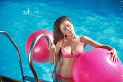 Το όμορφο προκλητικό θηλυκό πρότυπο με τα pilates fitballs που θέτουν μέσα κολυμπά Στοκ Φωτογραφίες