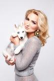 Το όμορφο προκλητικό σκυλί κατοικίδιων ζώων αγκαλιάσματος γυναικών makeup ντύνει ξανθό στοκ φωτογραφία