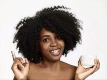 Το όμορφο πρότυπο μαύρων Αφρικανών με την άψογη ομαλή χροιά δερμάτων που ισχύει moisturiser αντιμετωπίζει την κρέμα στο μάγουλό τ στοκ εικόνες με δικαίωμα ελεύθερης χρήσης