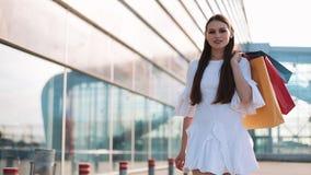 Το όμορφο πρότυπο μόδας στο άσπρο φόρεμα θέτει με τις τσάντες αγορών πριν από ένα σύγχρονο κτήριο γυαλιού κίνηση αργή φιλμ μικρού μήκους