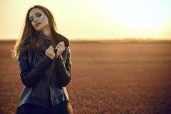 Το όμορφο πρότυπο glam με τη μακρυμάλλη μαύρη κάλυψη φθοράς ντύνει και μοντέρνο σακάκι δέρματος που στέκεται στον εγκαταλειμμένο  Στοκ Φωτογραφίες