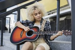Το όμορφο, σγουρό κορίτσι αφροαμερικάνων επιθυμεί να παίξει την κιθάρα η οδός στοκ εικόνες
