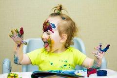 Το όμορφο σχέδιο μικρών κοριτσιών στο λεύκωμα, το λερωμένα πρόσωπο και τα χέρια χρωματίζουν, μάτια Στοκ φωτογραφία με δικαίωμα ελεύθερης χρήσης