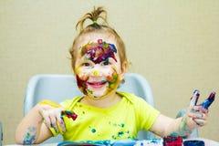 Το όμορφο σχέδιο μικρών κοριτσιών στο λεύκωμα, το λερωμένα πρόσωπο και τα χέρια χρωματίζουν, μάτια Στοκ Εικόνες