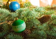 Το όμορφο υπόβαθρο Χριστουγέννων με τους κώνους πεύκων, τα παιχνίδια Χριστουγέννων, το κιβώτιο δώρων και το έλατο διακλαδίζεται,  Στοκ φωτογραφίες με δικαίωμα ελεύθερης χρήσης