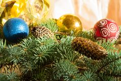 Το όμορφο υπόβαθρο Χριστουγέννων με τους κώνους πεύκων, τα παιχνίδια Χριστουγέννων, το κιβώτιο δώρων και το έλατο διακλαδίζεται,  Στοκ εικόνα με δικαίωμα ελεύθερης χρήσης