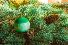 Το όμορφο υπόβαθρο Χριστουγέννων με τους κώνους πεύκων, τα παιχνίδια Χριστουγέννων, το κιβώτιο δώρων και το έλατο διακλαδίζεται,  Στοκ Εικόνες