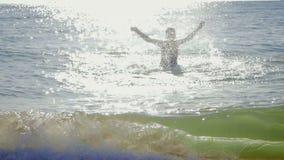 Το όμορφο, φίλαθλο κορίτσι σε ένα μαύρο μαγιό προκύπτει από τη θάλασσα απόθεμα βίντεο