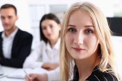 Το όμορφο χαμογελώντας εύθυμο κορίτσι στον εργασιακό χώρο φαίνεται κεκλεισμένων των θυρών Στοκ Εικόνα