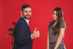 Το όμορφο χαμογελώντας ζεύγος με το κόκκινο αυξήθηκε στο κόκκινο υπόβαθρο Στοκ φωτογραφία με δικαίωμα ελεύθερης χρήσης