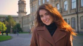 Το όμορφο χαμογελώντας καυκάσιο κορίτσι στέκεται μόνο στα sunlights πέρα από τα αστικά κτήρια και κρεμά ευτυχώς υπαίθρια απόθεμα βίντεο