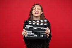 Το όμορφο χαμογελώντας κορίτσι στο μαύρο πουλόβερ γουνών που κρατά τα μάτια έκλεισε, κρατώντας την κλασική μαύρη παραγωγή ταινιών στοκ εικόνα