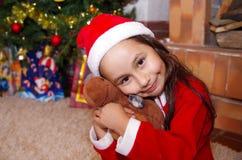 Το όμορφο χαμογελώντας μικρό κορίτσι που φορά Χριστούγεννα ντύνει, αγκαλιάζοντας μια άλκη teddy, με ένα υπόβαθρο χριστουγεννιάτικ Στοκ Φωτογραφίες