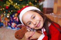 Το όμορφο χαμογελώντας μικρό κορίτσι που φορά Χριστούγεννα ντύνει, αγκαλιάζοντας μια άλκη teddy, με ένα υπόβαθρο χριστουγεννιάτικ Στοκ φωτογραφία με δικαίωμα ελεύθερης χρήσης