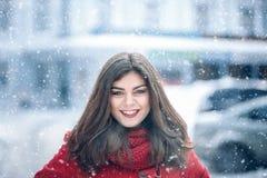 Το όμορφο χαμόγελο γυναικών brunette και χαίρεται στο χιόνι για την οδό πόλεων DTE Στοκ Εικόνα