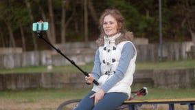 Το όμορφο χαμόγελο κοριτσιών παίρνει τη μόνη εικόνα selfie με το έξυπνο τηλέφωνο κινητό στο πάρκο απόθεμα βίντεο