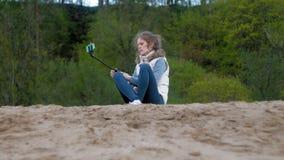 Το όμορφο χαμόγελο κοριτσιών παίρνει τη μόνη εικόνα selfie με το έξυπνο τηλέφωνο κινητό στην όχθη ποταμού απόθεμα βίντεο