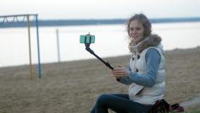 Το όμορφο χαμόγελο κοριτσιών παίρνει τη μόνη εικόνα selfie με το έξυπνο τηλέφωνο κινητό στην όχθη ποταμού φιλμ μικρού μήκους