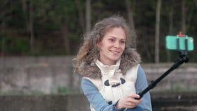 Το όμορφο χαμόγελο κοριτσιών παίρνει τη μόνη εικόνα selfie με το έξυπνο τηλέφωνο κινητό στο πάρκο φιλμ μικρού μήκους