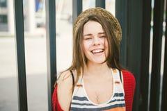 Το όμορφο χαμόγελο νέων κοριτσιών, είναι ευτυχές, ευτυχής σε ένα καπέλο, ένα κόκκινο πουκάμισο πέρα από την πόλη Στοκ εικόνες με δικαίωμα ελεύθερης χρήσης