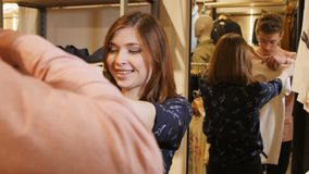 Το όμορφο χαρούμενο κορίτσι παίρνει τη γρήγορη μοντέρνη μπλούζα από το ράφι απόθεμα βίντεο