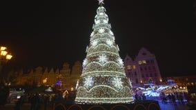 Το όμορφο χριστουγεννιάτικο δέντρο με τα ζωηρόχρωμα παιχνίδια και τις ακτινοβολώντας γιρλάντες, άνθρωποι περπατά στο τετράγωνο αγ απόθεμα βίντεο