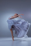 Το όμορφο ballerina που χορεύει στο μπλε μακρύ φόρεμα Στοκ Φωτογραφίες