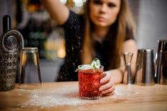 Το όμορφο barista τελειώνει την προετοιμασία του ρόδινου οινοπνευματώδους κοκτέιλ με την προσθήκη έναν πικρού της κονιοποιημένης  Στοκ Εικόνες