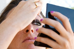 Το όμορφο brunette εφαρμόζει τη σκιά ματιών. Στοκ Εικόνα