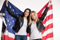Το όμορφο brunette και ξανθός κρατά την ΑΜΕΡΙΚΑΝΙΚΗ σημαία στοκ φωτογραφίες