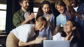 Το όμορφο brunette λειτουργεί με τον υπολογιστή και γελώντας, η ομάδα της έρχεται να την συγχάρει στα καλά αποτελέσματα, άνθρωποι απόθεμα βίντεο