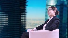 Το όμορφο brunette με τα γυαλιά που κάθονται στο στούντιο σε ένα επιχειρησιακό κοστούμι και δίνει τις συνεντεύξεις με ένα χαμόγελ απόθεμα βίντεο