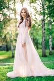 Το όμορφο brunette νυφών νέων κοριτσιών στη λεπτή νυφική εσθήτα μπουντουάρ της δαντέλλας και του Tulle στο μπεζ χρώμα είναι υπαίθ Στοκ φωτογραφία με δικαίωμα ελεύθερης χρήσης