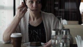 Το όμορφο brunette πίνει τον καφέ από ένα φλυτζάνι και την κατανάλωση cheesecake φιλμ μικρού μήκους