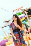 Το όμορφο brunette σε ένα μακρύ φόρεμα στην παραλία κοντά στο φραγμό ή πηγαίνει έννοια της ψυχαγωγίας και της αναψυχής Στοκ Εικόνες