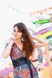 Το όμορφο brunette σε ένα μακρύ φόρεμα στην παραλία κοντά στο φραγμό ή πηγαίνει έννοια της ψυχαγωγίας και της αναψυχής Στοκ Φωτογραφία