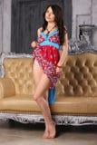 Το όμορφο brunette σε ένα φωτεινό φόρεμα στέκεται κοντά σε έναν καναπέ δέρματος Στοκ φωτογραφία με δικαίωμα ελεύθερης χρήσης