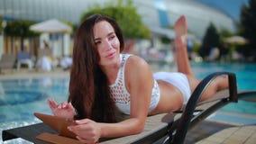 Το όμορφο brunette στο άσπρο μπικίνι χαλαρώνει στην πισίνα καρεκλών γεφυρών πλησίον απόθεμα βίντεο