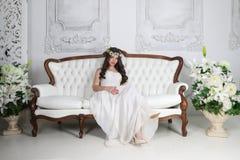 Το όμορφο brunette στο στεφάνι και στο μακρύ φόρεμα θέτει στον καναπέ Στοκ Εικόνες