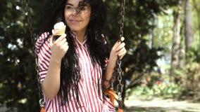 Το όμορφο brunette τρώει το παγωτό σε μια ταλάντευση στο πάρκο φιλμ μικρού μήκους