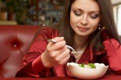 το όμορφο brunette τρώει το κορίτ&si Στοκ Φωτογραφίες