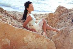 Το όμορφο brunette φορά το κομψό φόρεμα με το κόσμημα, που θέτει στη θερινή παραλία Στοκ Φωτογραφίες