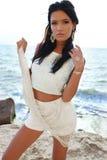 Το όμορφο brunette φορά το κομψό φόρεμα με το κόσμημα, που θέτει στη θερινή παραλία Στοκ Φωτογραφία