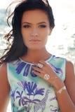 Το όμορφο brunette φορά το κομψό φόρεμα με το κόσμημα, που θέτει στη θερινή παραλία Στοκ φωτογραφία με δικαίωμα ελεύθερης χρήσης