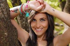 Το όμορφο brunette Headshot, που στέκεται μεταξύ των δέντρων, γυμνά ξεφλουδισμένα όπλα επάνω από το κεφάλι θέτει, εξετάζοντας sen Στοκ Φωτογραφία